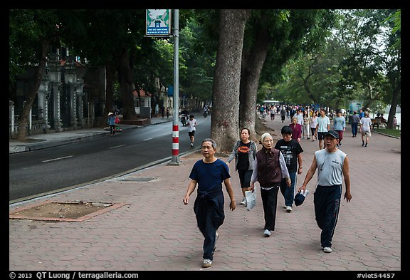 Numerous people walk counter-clockwise around Hoang Kiem Lake. Hanoi, Vietnam (color)