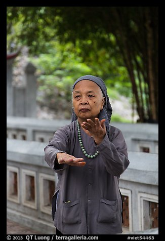 Elderly woman doing Tai Chi moves. Hanoi, Vietnam (color)