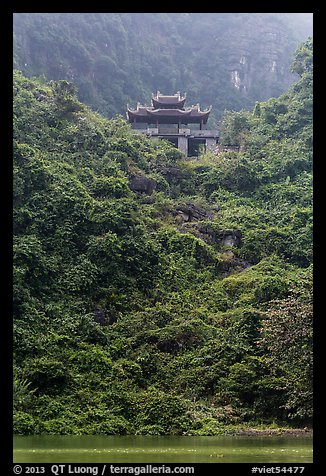Temple perched on lush hill, Trang An. Ninh Binh,  Vietnam (color)