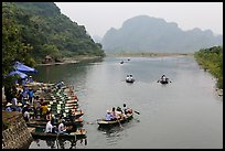 Groups leaving wharf on boats, Trang An. Ninh Binh,  Vietnam (color)