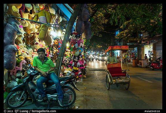 Street at night with motorcycle and cyclo, old quarter. Hanoi, Vietnam (color)