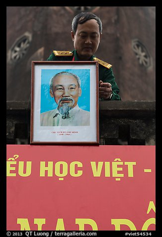 Officer hanging a picture of Ho Chi Minh, Hanoi Citadel. Hanoi, Vietnam (color)