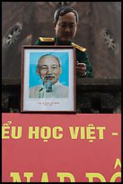 Officer hanging a picture of Ho Chi Minh, Hanoi Citadel. Hanoi, Vietnam ( color)