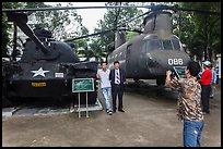 Tourists pose with tanks and helicopters, War Remnants Museum, district 3. Ho Chi Minh City, Vietnam (color)