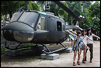 Young women posing with helicopter, War Remnants Museum, district 3. Ho Chi Minh City, Vietnam (color)