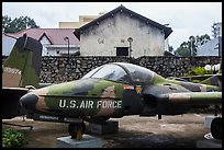 Warplane and wall with barbed wire, War Remnants Museum, district 3. Ho Chi Minh City, Vietnam (color)