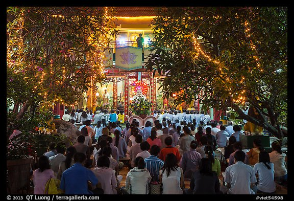 Worshippers at Quoc Tu Pagoda by night, district 10. Ho Chi Minh City, Vietnam (color)