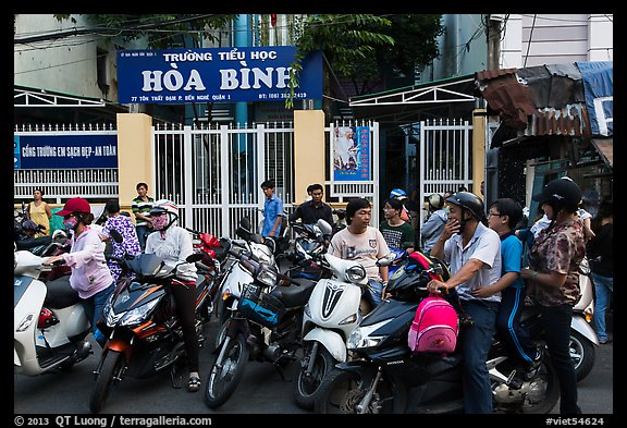 School entrance with parents waiting on motorbikes. Ho Chi Minh City, Vietnam (color)