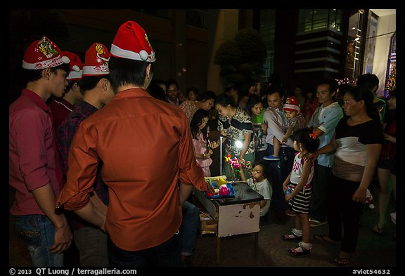 People gather around street hawker on Christmas eve. Ho Chi Minh City, Vietnam (color)