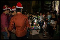 People gather around street hawker on Christmas eve. Ho Chi Minh City, Vietnam ( color)