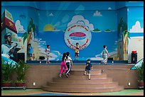 Children on stage next to militaristic mural, Dam Sen Water Park, district 11. Ho Chi Minh City, Vietnam ( color)