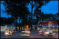 Blurred motorbikes at dusk and tall trees next to Van Hoa Park. Ho Chi Minh City, Vietnam (color)