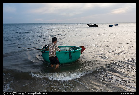 Man holding coracle boat. Mui Ne, Vietnam (color)