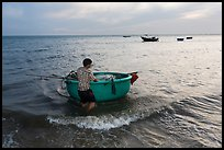 Man holding coracle boat. Mui Ne, Vietnam ( color)