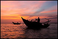 Men on fishing skiffs under bright sunset skies. Mui Ne, Vietnam (color)