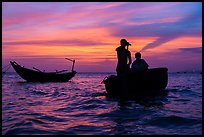 Men silhouetted paddling coracle boat at sunset. Mui Ne, Vietnam ( color)