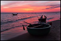 Fishermen bringing round coracle boat to shore at sunset. Mui Ne, Vietnam (color)