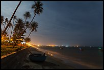 Beach, palm trees and coracle boats at night. Mui Ne, Vietnam (color)
