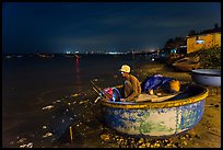 Man working on coracle boat at night. Mui Ne, Vietnam (color)