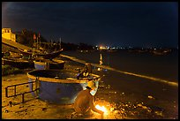 Man with fire next to coracle boat at night. Mui Ne, Vietnam (color)