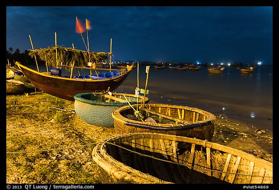 Coracle boats and fishing fleet at night. Mui Ne, Vietnam (color)