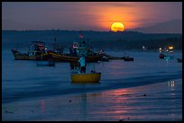 Fisherman paddling on coracle boat towards fishing boats at moonset. Mui Ne, Vietnam ( color)