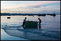Fishermen pushing coracle boat at dawn. Mui Ne, Vietnam (color)