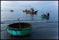 Coracle and fishing boats at dawn. Mui Ne, Vietnam (color)