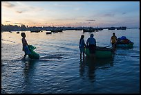 Fishermen using coracle boats to transport cargo at dawn. Mui Ne, Vietnam (color)