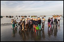 Women gather on beach to collect freshly caught fish. Mui Ne, Vietnam (color)