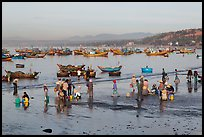 Hawkers gather on mirror-like beach in early morning. Mui Ne, Vietnam (color)