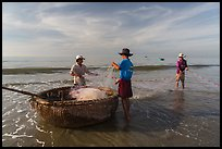 Fishermen folding fishing net into coracle boat. Mui Ne, Vietnam ( color)