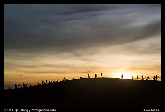 Tourists watching sunset from dune. Mui Ne, Vietnam (color)