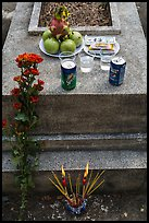 Grave with offerings of incense, flowers, drinks, fruit, and fake money. Ben Tre, Vietnam ( color)