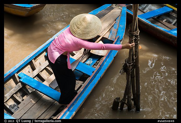 Woman in ao dai reaching to bamboo poles from boat. My Tho, Vietnam