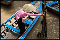 Woman in ao dai reaching to bamboo poles from boat. My Tho, Vietnam (color)