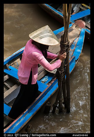 Woman in Ao Ba Ba holding from boat to bamboo poles. My Tho, Vietnam (color)