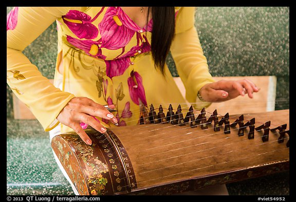 Close up of hands playing plucked zither. My Tho, Vietnam (color)