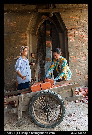 Workers loading bricks out of brick oven. Mekong Delta, Vietnam (color)