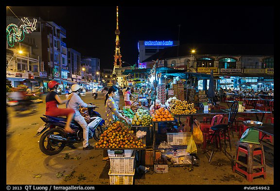Street market and telecomunication tower at night. Tra Vinh, Vietnam (color)