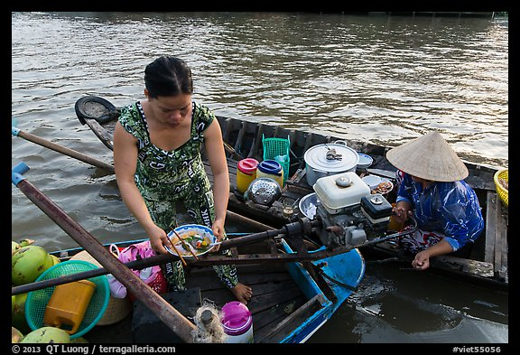 Woman gets bowl of noodles from floating market. Can Tho, Vietnam (color)