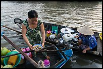 Woman gets bowl of noodles from floating market. Can Tho, Vietnam ( color)