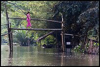Woman crossing monkey bridge. Can Tho, Vietnam ( color)