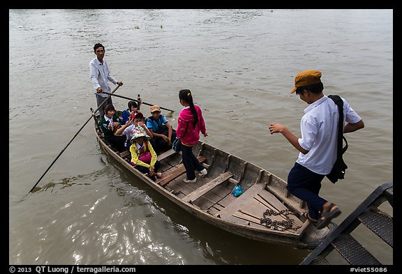 Schoolchildren stepping onto boat. Can Tho, Vietnam (color)