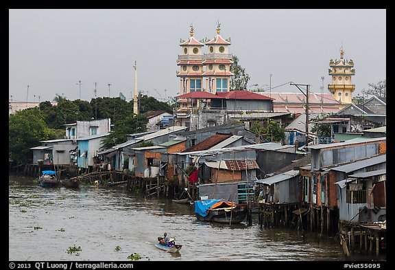 Riverside houses on stilts and Cao Dai temple. Mekong Delta, Vietnam (color)