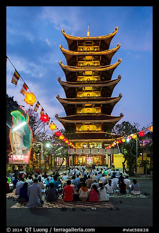 Worshippers and seven story  Quoc Tu pagoda at dusk. Ho Chi Minh City, Vietnam (color)