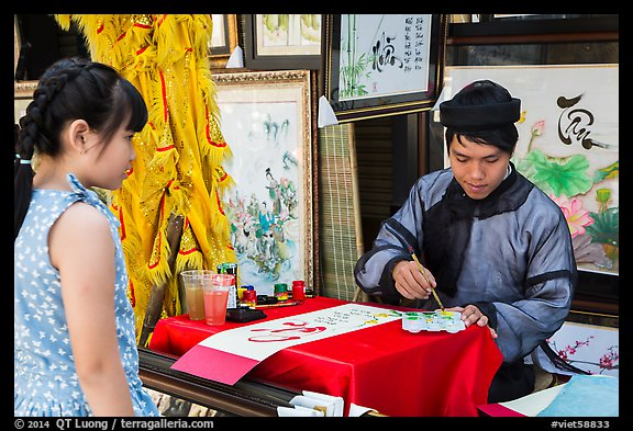 Caligrapher draws Tet greetings as woman looks on. Ho Chi Minh City, Vietnam (color)