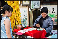 Caligrapher draws Tet greetings as woman looks on. Ho Chi Minh City, Vietnam ( color)