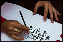 Feminine hand draws Lunar New Year greetings in fancy writing. Ho Chi Minh City, Vietnam ( color)