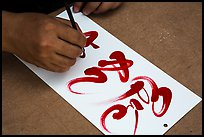 Hands drawing Tet (Lunar New Year) greetings in Chinese characters. Ho Chi Minh City, Vietnam ( color)
